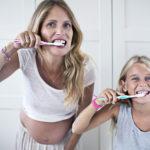 Mutter und Kind putzen gemeinsam Zähne